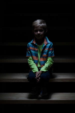 View of lonely boy sitting on staircase photo