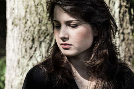 Portrait of young, sad woman in black photo