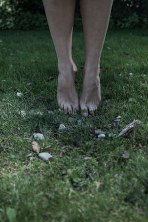 hanged woman: Close up of toes touching the grass in the garden Stock Photo