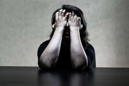 Sorrowfull young woman hiding her face in hands photo
