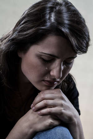 Dark portrait of beautiful crying woman, vertical photo
