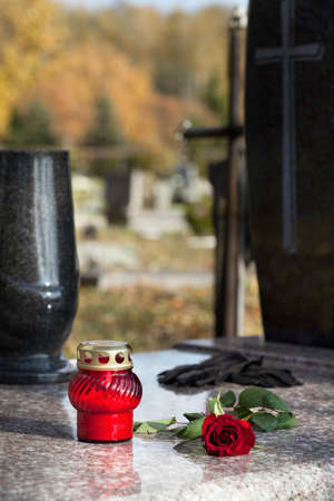 Red candle and rose on the grave made of stone photo