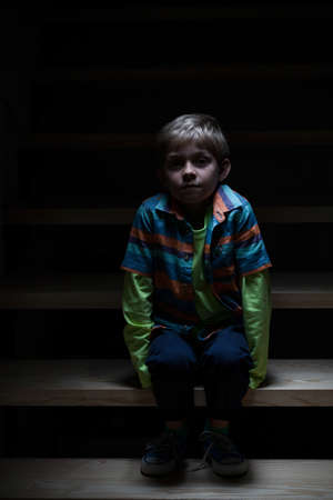 Boy alone on stairs at night, vertical photo