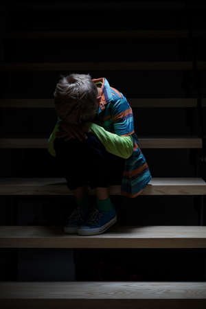 View of crying boy sitting on staircase Foto de archivo