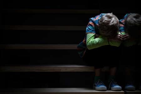 niños tristes: Boy en una escalera en la noche, horizontal