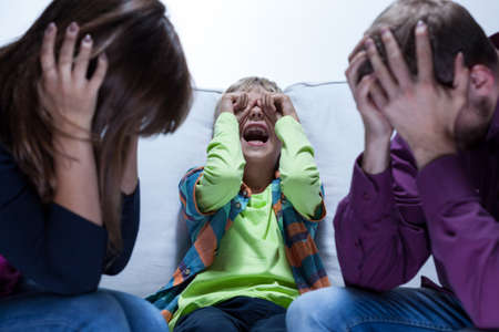 angry kid: View of screaming boy and tired parents Stock Photo