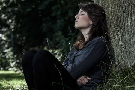 Portrait of young sad woman sitting under the tree photo