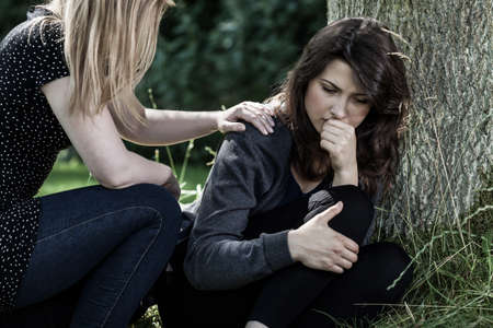 mourn: Young woman comforting her mourning friend Stock Photo