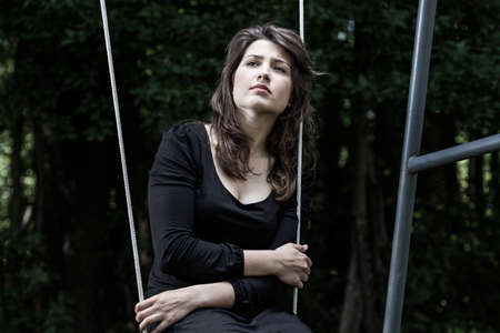 Young, sad woman sitting on a swing photo