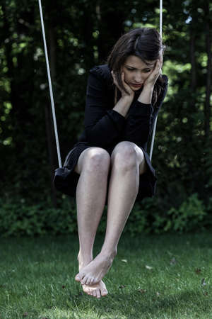 Young worried woman in black sitting on swing