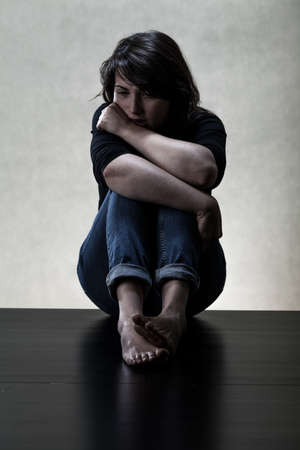 Depressed young woman sitting on the floor Imagens