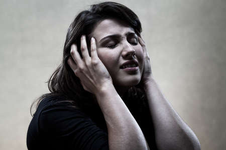 Portrait of young crying woman in black photo