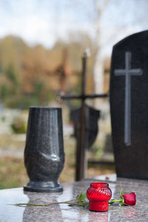 cremation: Stone monument with flower and candle on the cemetery Stock Photo