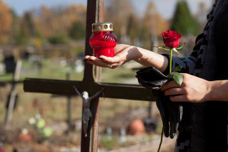 angel cemetery: Woman is putting the snitch on the grave of close person