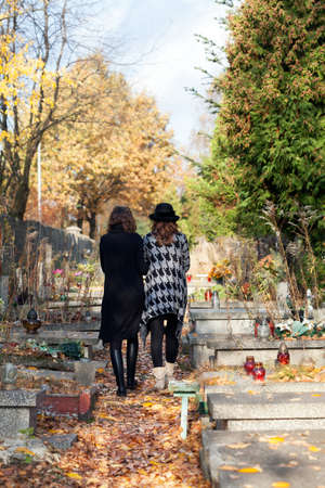 tomb empty: Sisters in mourning walking at the cemetery after mother death