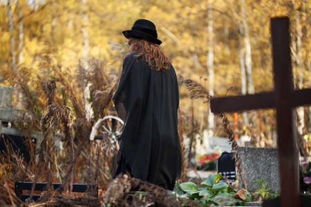woeful: Woman in black walking alone and helpless at the cemetery Stock Photo