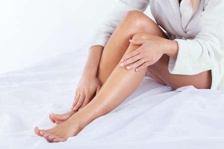 piernas mujer: Vista horizontal de la mujer que usa crema para el cuerpo Foto de archivo