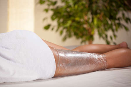 body care: Body wrapping in a spa room, horizontal Stock Photo