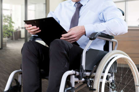 Disabled office worker sitting on a wheelchair photo