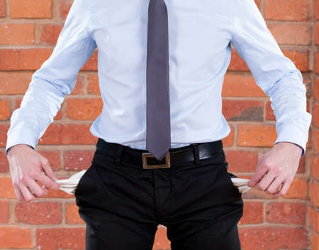 troublemaker: Businessman in suit with no money in pockets Stock Photo
