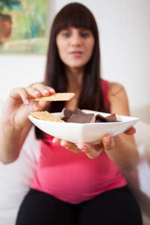 Young pregnant woman holding bowl with sweets photo