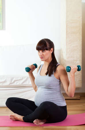 Young pregnant girl working out with dumbbells at home photo