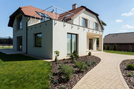 Modern suburban house with green minimalist garden  스톡 콘텐츠