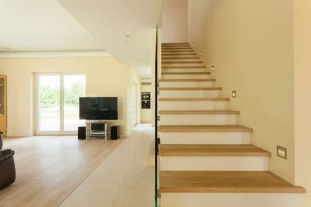 Spacious well lit living room with staircase photo