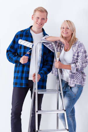 Smiling young couple painting a room, vertical photo