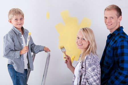 flannel: Portrait of a smiling family painting a wall Stock Photo