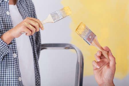tremp�e: Close-up de mains avec des pinceaux tremp�s dans la peinture jaune Banque d'images