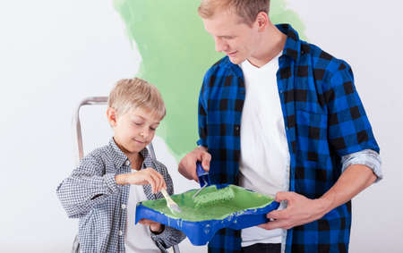 redecorating: Father and his little son redecorating the house together