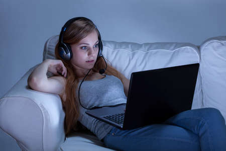 skype: Girl with headphones using computer at night