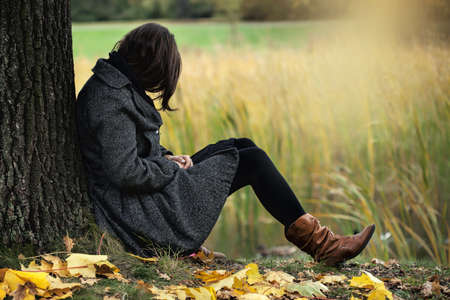 Woman contemplating alone in the autumn park