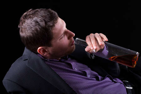 Horizontal view of young man addicted to alcohol photo