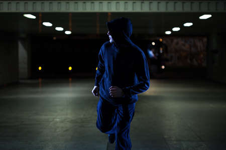 Mugger running in the underpass at night Stock Photo