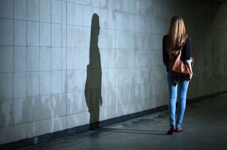asustado: Vista de una mujer caminando sola por la noche