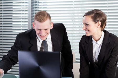 workmate: Smiling co-workers using laptop in their job