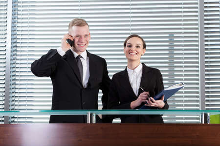 workmate: Horizontal view of smiling business people during their work Stock Photo