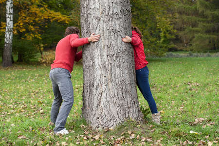 hide and seek: Friends playing around the tree during autumn walk