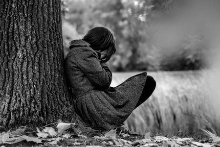 Sad woman crying after break up in the park Stock Photo
