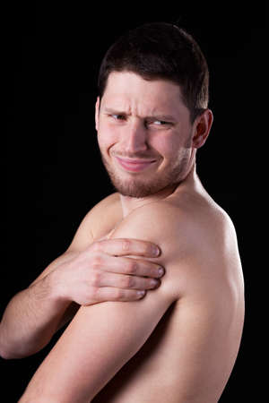 Young man suffering from pain of rotator cuff photo