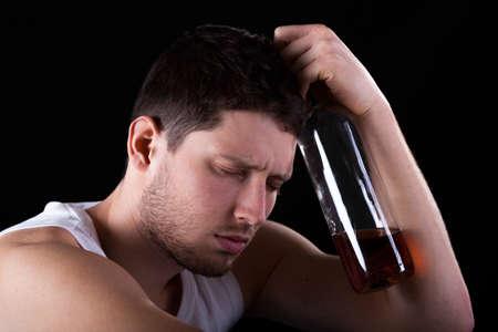 hombre solitario: Hombre inconsciente con una botella de alcohol caro