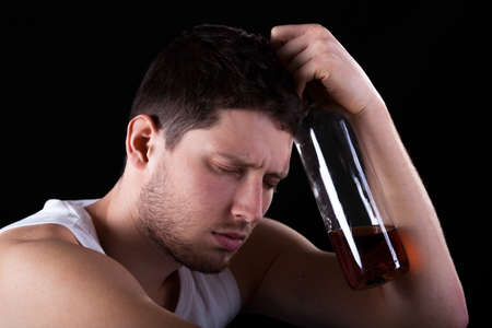 Unconscious man with bottle of expensive alcohol photo