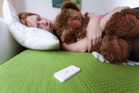 embarrassing: Crying teenager cuddling a teddy bear with pregnancy test