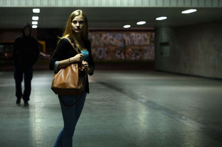 fear woman: Danger in the underpass at night, horizontal