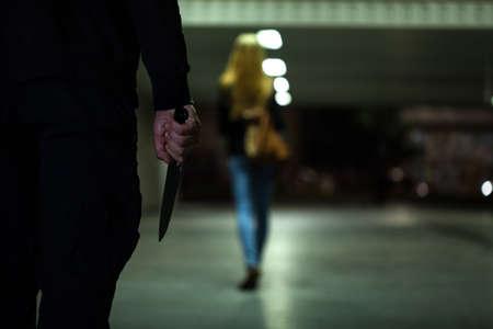 次の女性の夜のナイフを持つ男