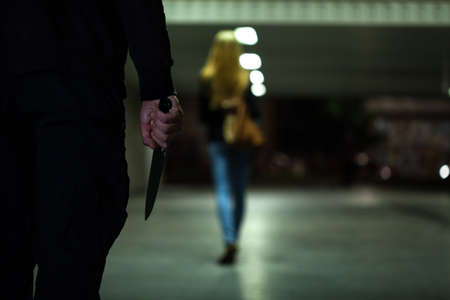 city in the night: Man with knife following woman at night
