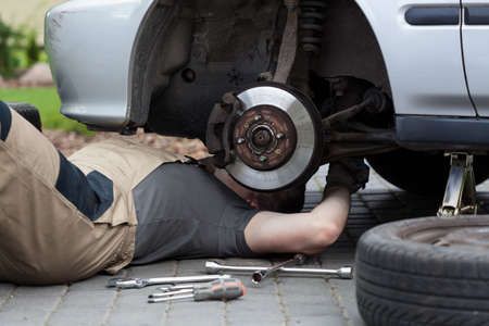 accident at work: Horizontal view of mechanic repairing car wheel Stock Photo