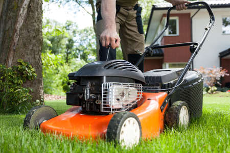 mower: Turning on the lawn mower by gardener Stock Photo